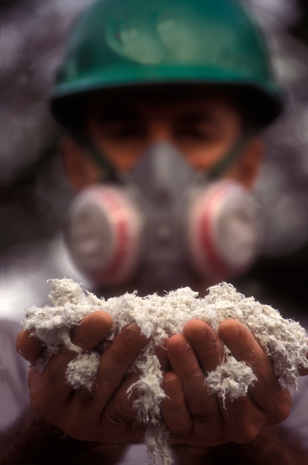 Man wearing mask holding asbestos in hands